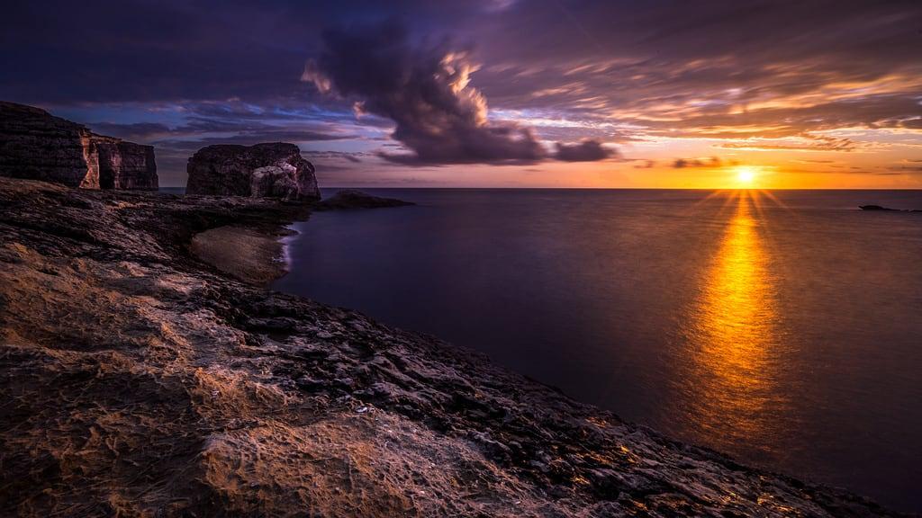 Immagine di Fungus Rock. longexposure travel sunset sea sky orange cliff seascape motion nature rock clouds landscape geotagged photography photo rocks europe mt natural sony malta fungus fullframe onsale ultrawide a7 gozo sanlawrenz sonya7 sonyfe1635