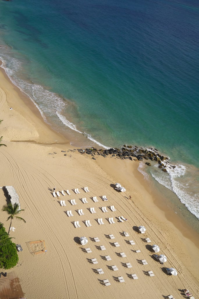 Image of Condado Beach. beach sand chairs ocean sea waves surf blue shore breakwater